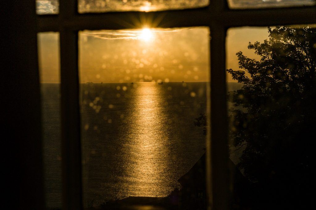 Photograph of the sun setting over the sea through a window